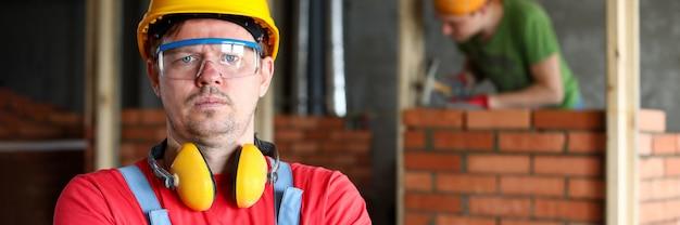 Portrait de contremaître concentré debout avec les bras croisés sur chantier. mur de bâtiment travailleur avec des briques rouges. copiez l'espace dans le côté droit. concept de rénovation
