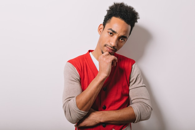 Portrait de cool jeune homme afro-américain pose sur un mur gris avec des émotions sérieuses