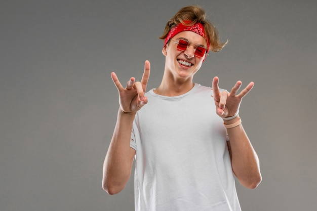 Un portrait de cool young caucasian man with short red curly hair in white t-shirt, red glasses show a doigts isolated on a grey