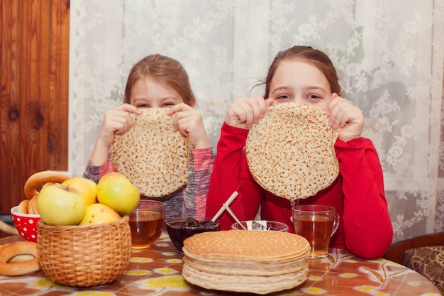 Portrait de copines à table avec pile de crêpes et thé