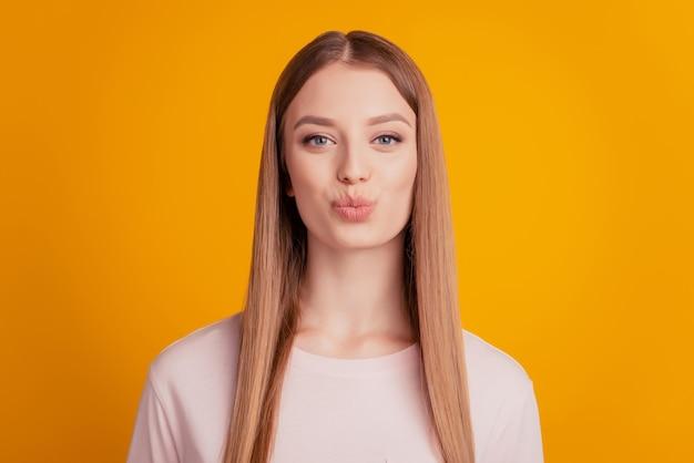 Portrait de coquette fille rêveuse dame souffle baiser d'air sur fond jaune