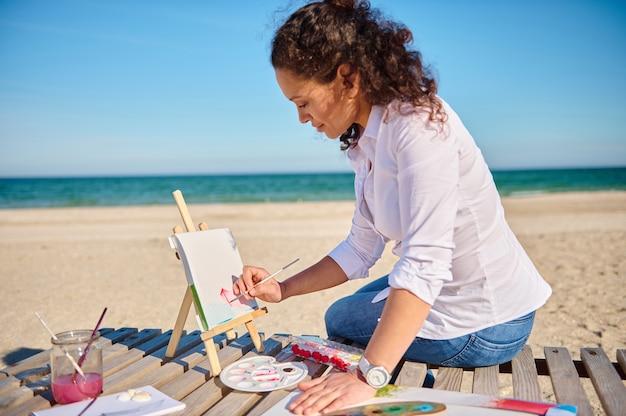 Portrait de côté d'une belle femme peintre afro-américaine dessinant sur toile en plein air sur la surface de la mer