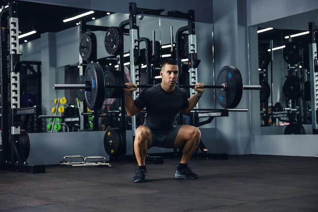 Un portrait de côté d'un bodybuilder en gris faisant des squats à l'aide d'une barre dans une salle de sport pour entraîner ses jambes et son dos