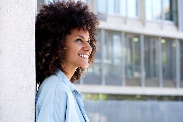 Portrait côté, de, femme souriante, debout, dehors, par, bâtiment urbain