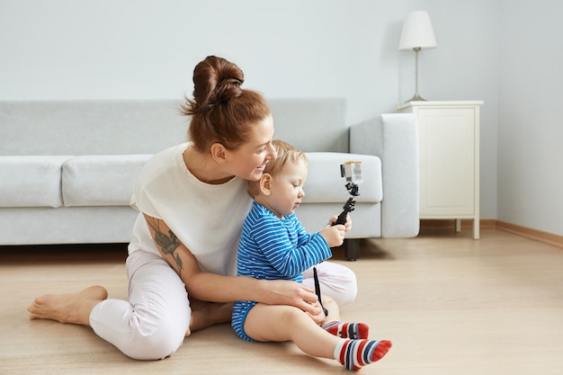 Portrait de côté de l'heureuse jeune mère caucasienne et son fils assis sur le sol à la maison, faisant selfie. femme souriante en vêtements blancs serrant son bébé. enfant prenant une photo avec un bâton de selfie.