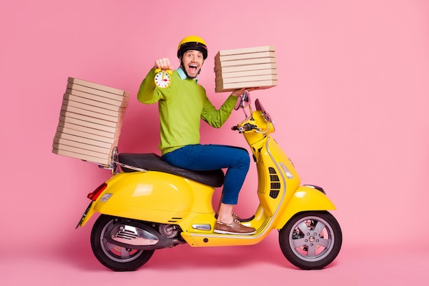 Portrait côté profil de guy drive cyclomoteur apportant pile pizza hold réveil