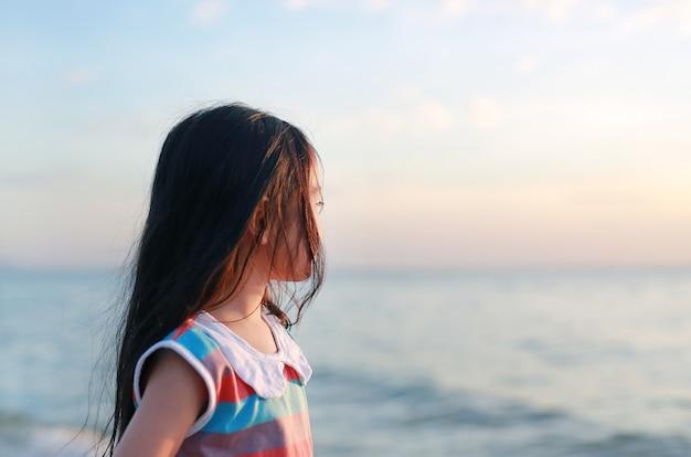 Portrait côté vue petite fille enfant debout sur la plage à la lumière du coucher du soleil avec regarder de mer.