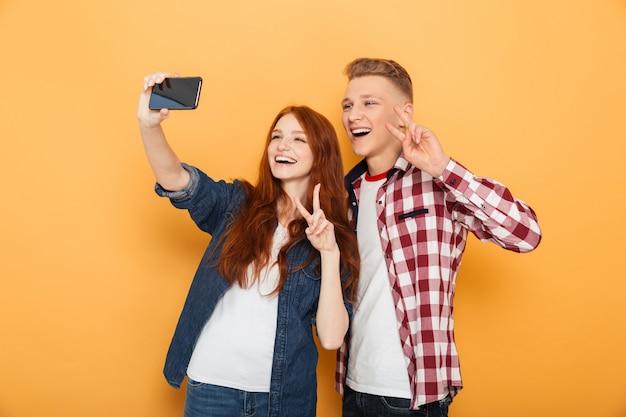Portrait d'un couple d'adolescents heureux prenant selfie