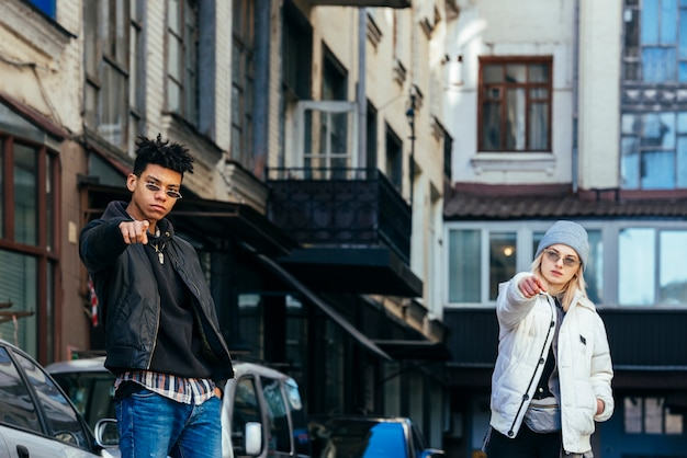 Portrait d'un couple d'adolescents à la mode, pointant leurs doigts vers la caméra