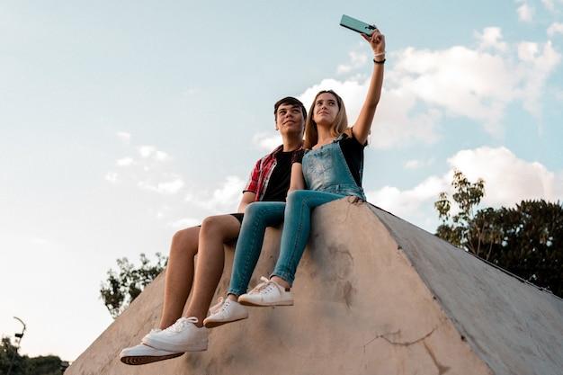Portrait d'un couple d'adolescents prenant un selfie dans un parc urbain.