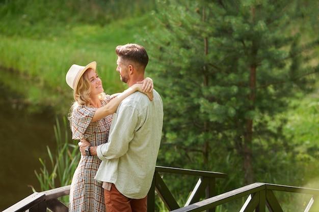 Portrait de couple adulte romantique embrassant et se regardant tout en posant au bord du lac à l'extérieur dans un paysage de campagne rustique