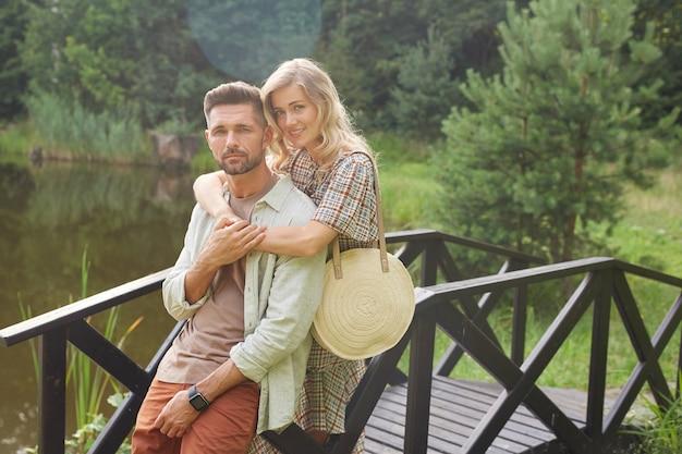 Portrait de couple adulte romantique embrassant tout en posant sur un pont en bois au bord du lac dans un paysage de campagne rustique