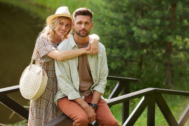 Portrait de couple adulte romantique embrassant tout en posant sur un pont en bois au bord du lac dans un paysage rustique