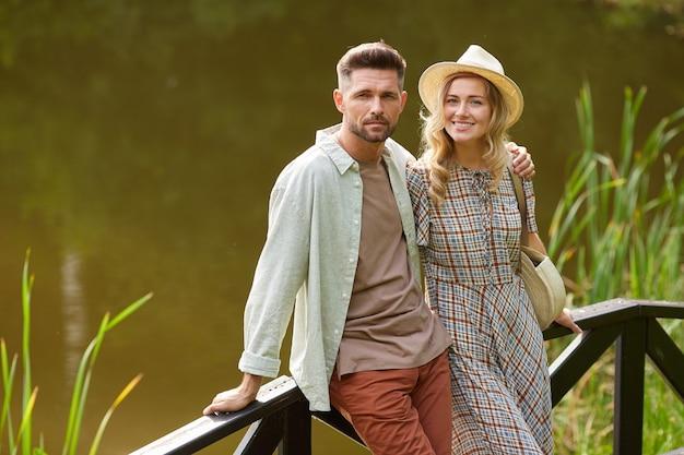 Portrait de couple adulte romantique tout en posant au bord du lac à l'extérieur dans un décor rustique