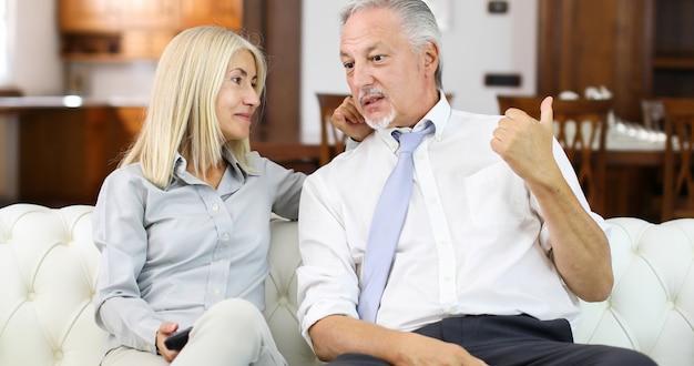 Portrait d'un couple d'âge mûr heureux dans leur maison devant la télé ensemble