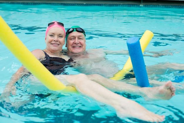 Portrait de couple d'âge mûr natation avec nouilles de piscine