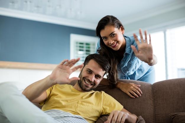 Portrait de couple en agitant les mains dans le salon à la maison