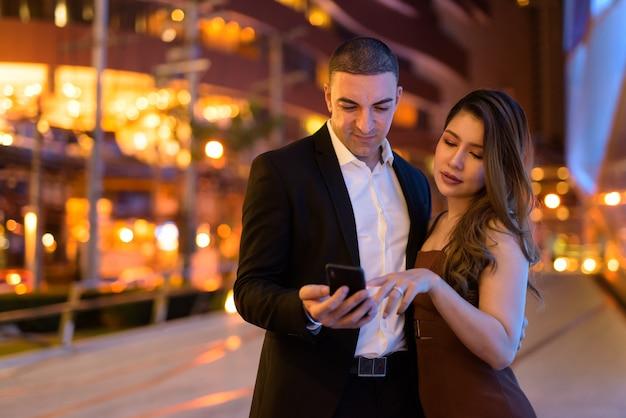 Portrait de couple à l'aide de téléphone à l'extérieur la nuit dans la ville de bangkok en thaïlande