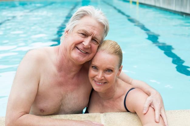 Portrait de couple aimant se penchant au bord de la piscine