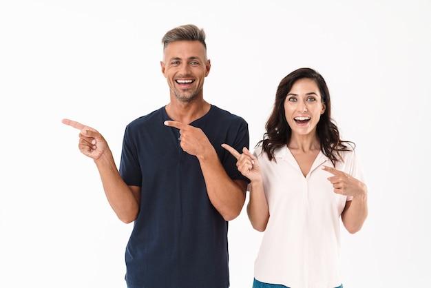 Portrait d'un couple d'amoureux adultes émotionnel choqué pointant isolé sur un mur blanc.