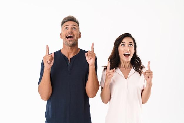 Portrait d'un couple d'amoureux adultes émotionnel surpris pointant isolé sur un mur blanc.