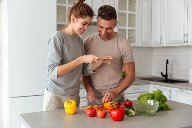 Portrait d'un couple d'amoureux heureux cuisiner ensemble la salade