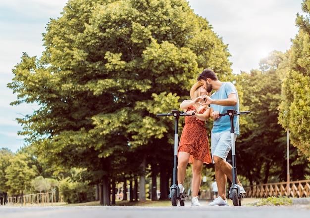 Portrait de couple amoureux s'embrasser à l'aide d'un scooter électrique dans le parc