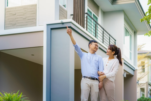Portrait de couple asiatique marchant étreindre et pointant ensemble à la recherche de plaisir devant leur nouvelle maison pour commencer une nouvelle vie. concept de famille, âge, maison, immobilier et personnes.