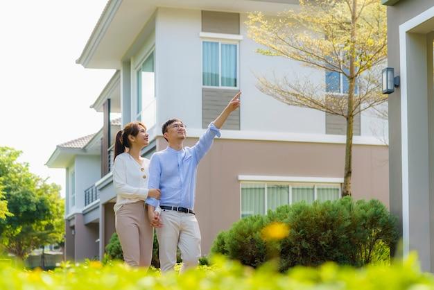 Portrait de couple asiatique marchant étreindre et pointant ensemble à la recherche de plaisir devant leur nouvelle maison pour commencer une nouvelle vie.