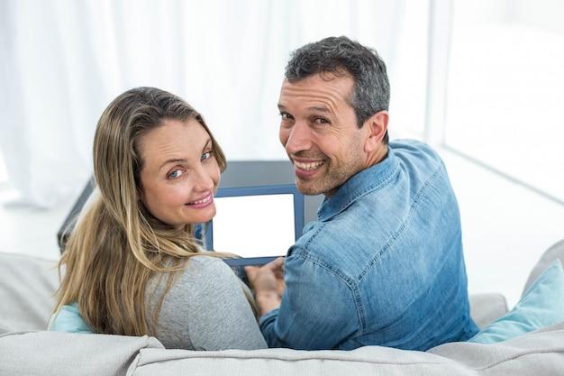 Portrait de couple assis sur le canapé et à l'aide de tablette numérique