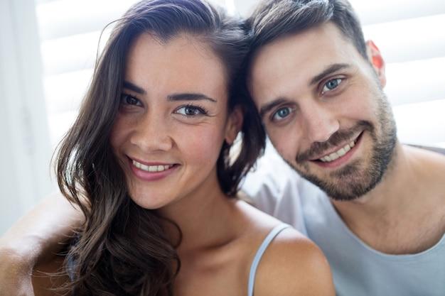 Portrait de couple assis dans la chambre à la maison