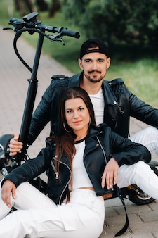 Portrait d'un couple assis près de scooters électriques, profitant du temps dans la nature ensemble, deux amoureux sur des scooters électriques.les gens sur des scooters.