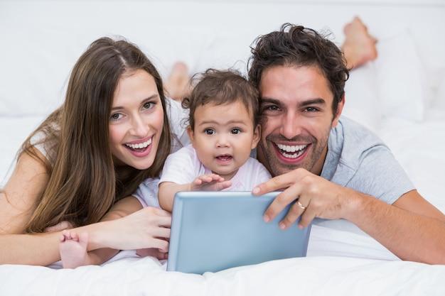 Portrait de couple avec bébé et tablette