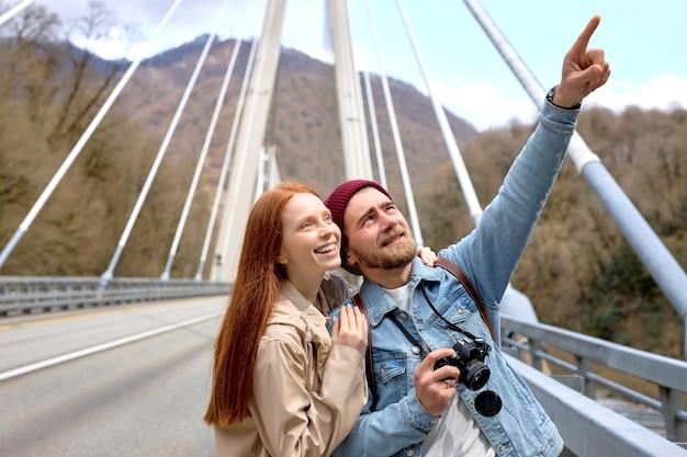 Portrait d'un couple caucasien en tenue décontractée marchant sur le pont, en contemplation des montagnes, des paysages autour. beau mâle pointant le doigt sur le côté, montrant quelque chose à sa petite amie