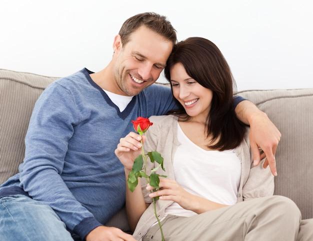 Portrait d'un couple charmant en regardant une rose rouge