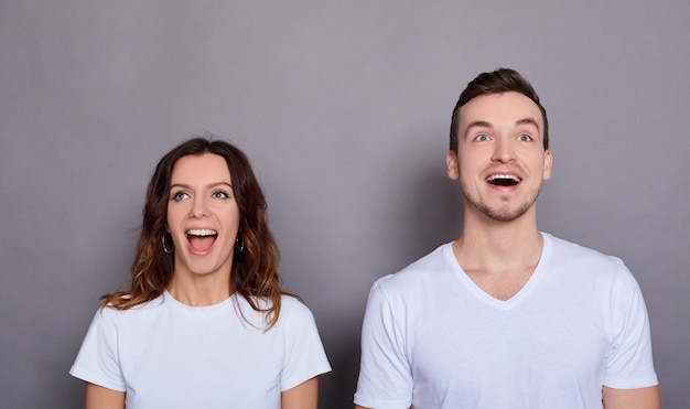 Portrait d'un couple étonné homme et femme en t-shirts blancs basiques