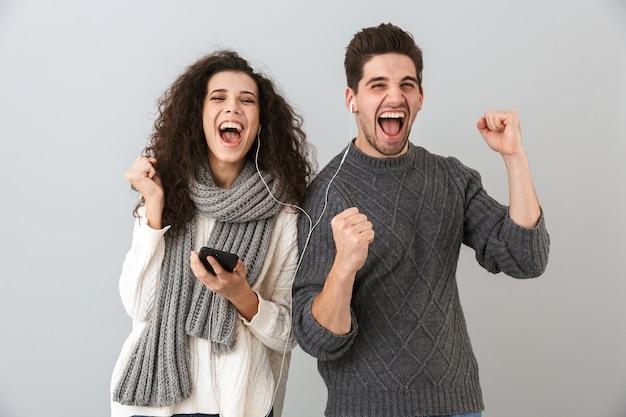 Portrait de couple extatique homme et femme écoutant de la musique avec des écouteurs et dansant, isolé sur mur gris