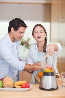 Portrait d'un couple faisant des jus de fruits frais