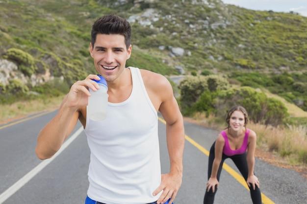 Portrait d'un couple en forme debout sur la route