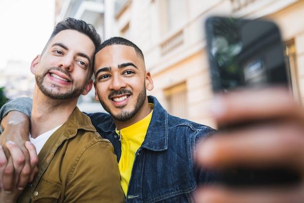 Portrait d'un couple gay heureux, passer du temps ensemble et prendre un selfie avec un téléphone portable dans la rue.