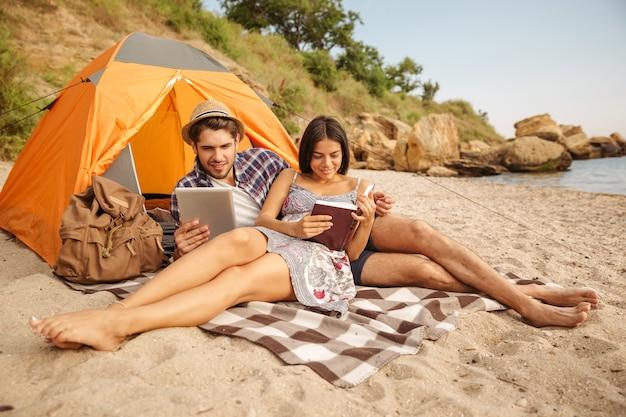 Portrait d'un couple heureux assis à la tente à l'aide d'une tablette et d'un livre de lecture