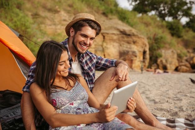 Portrait d'un couple heureux assis à la tente et utilisant une tablette tactile