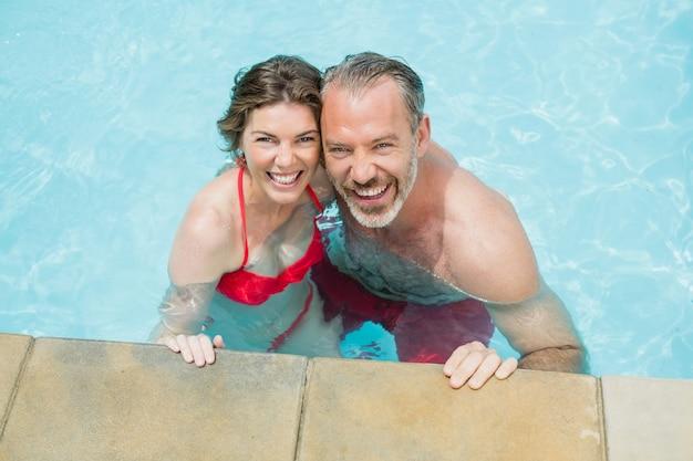 Portrait de couple heureux dans la piscine