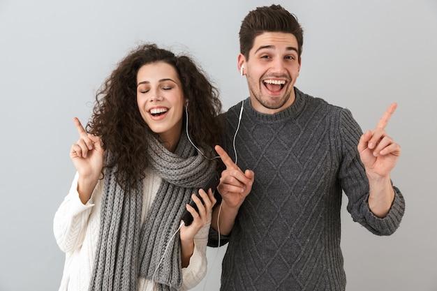 Portrait de couple heureux homme et femme écoutant de la musique avec des écouteurs et dansant, isolé sur mur gris