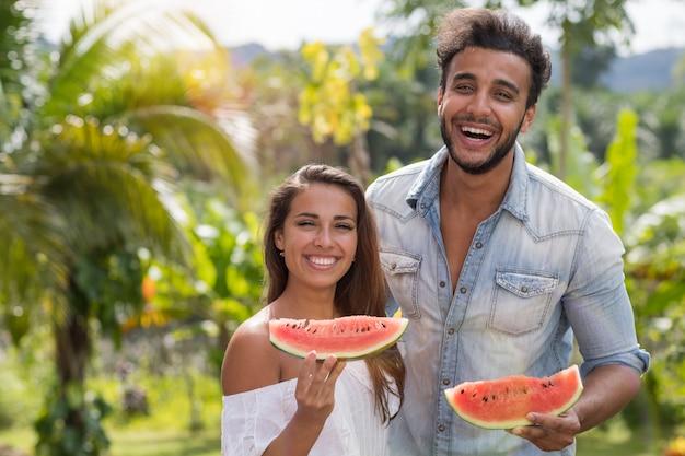 Portrait, couple heureux, manger, pastèque, ensemble, gai