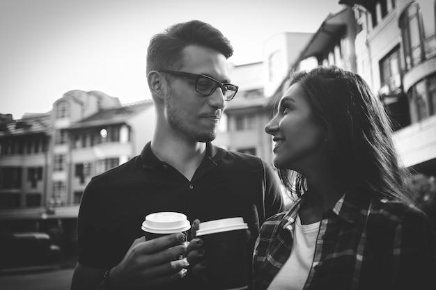 Portrait d'un couple heureux marchant dans la rue avec du café
