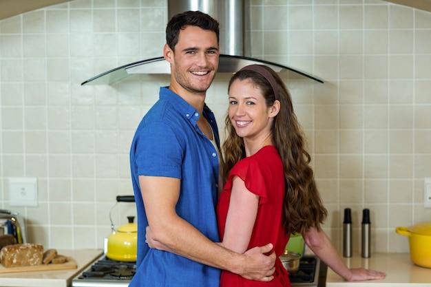 Portrait de couple heureux s'embrassant dans la cuisine à la maison