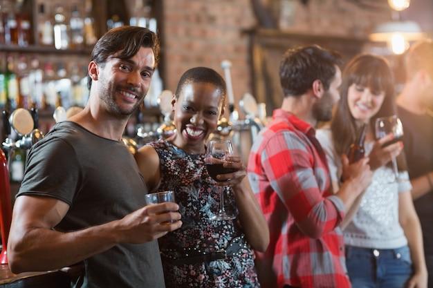 Portrait de couple heureux tenant des boissons