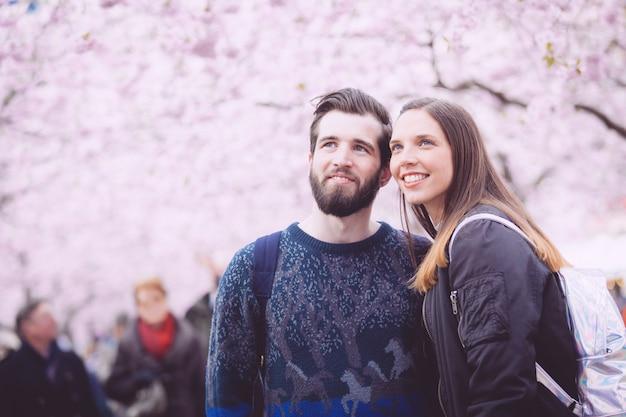 Portrait de couple hipster à stockholm avec des fleurs de cerisier
