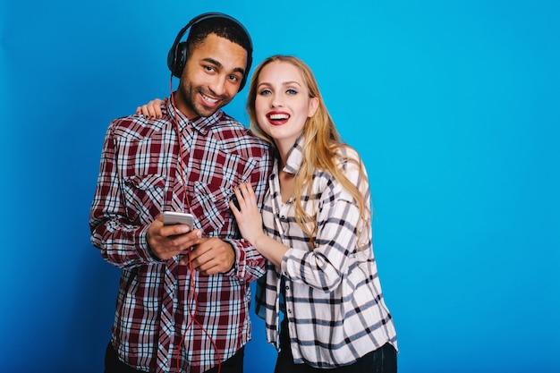 Portrait couple joyeux de jeune femme attarctive avec de longs cheveux blonds s'amusant avec beau mec écoutant de la musique avec des écouteurs. bonne humeur, souriant.